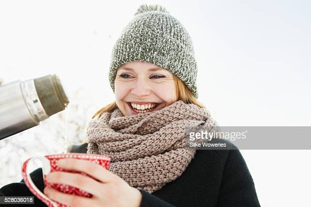 Happy young woman pouring hot beverage