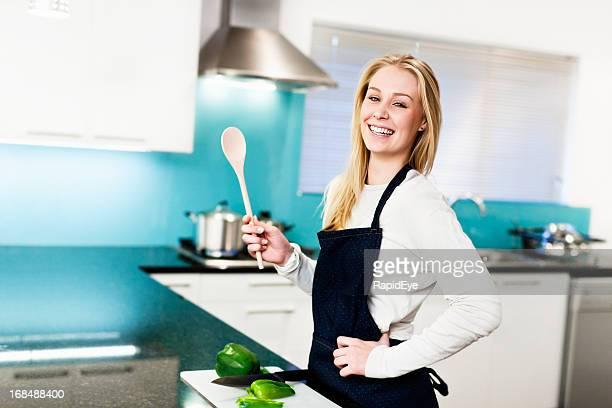 felice giovane donna preparare il cibo in cucina elegante - ventola di aspirazione foto e immagini stock