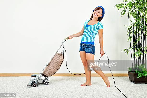 Happy Young Woman Pushing Vacuum Cleaner