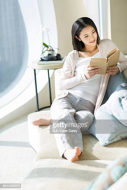 happy young woman reading a book on sofa - one young woman only stock pictures, royalty-free photos & images