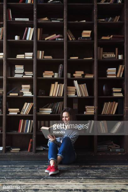 happy young woman reading in the library - book store stock photos and pictures