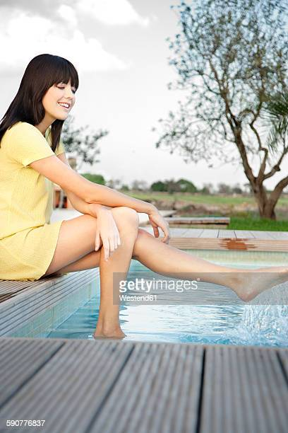 happy young woman relaxing at swimming pool - サンドレス ストックフォトと画像