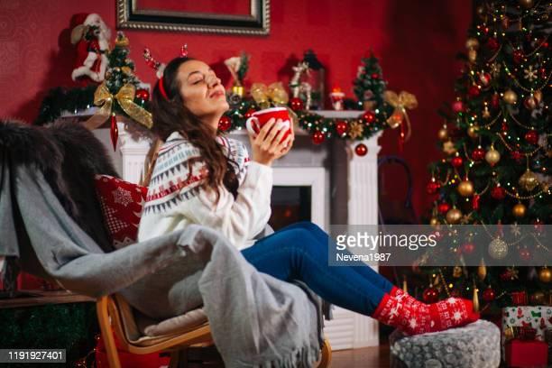 gelukkige jonge vrouw ontspannen bij de open haard en genieten van een kopje thee op een koude winterdag - christmas jumper stockfoto's en -beelden