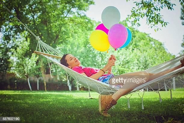 Happy young Frau entspannt sich in einer Hängematte im Garten