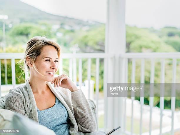 Glückliche junge Frau entspannen Sie auf dem Balkon