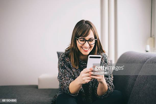 Happy young woman relaxing on the couch looking at her smartphone
