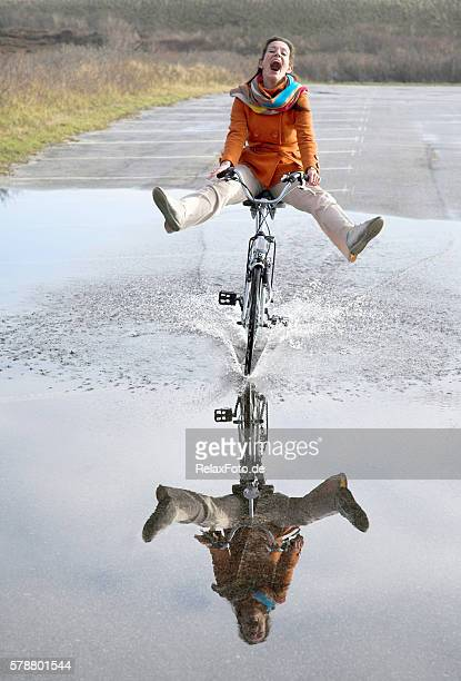 Happy Young Woman Riding Bicyle Through Large Puddle with Reflection