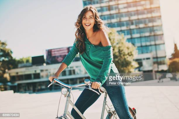 Happy young woman riding bike on a sunny day
