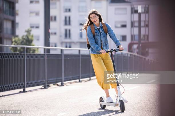 happy young woman riding electric scooter on a bridge - lebensstil stock-fotos und bilder