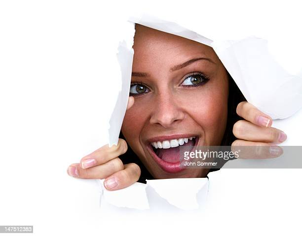happy young woman ripping through paper wall - caucasian appearance stock pictures, royalty-free photos & images