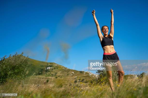 happy young woman runner celebrating running success - good posture stock pictures, royalty-free photos & images