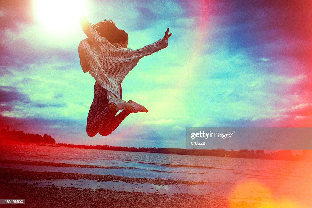 Felice giovane donna di correre e saltare sulla spiaggia : Foto stock