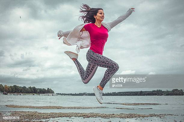 happy young woman running and jumping on the beach - yoga pants stock photos and pictures