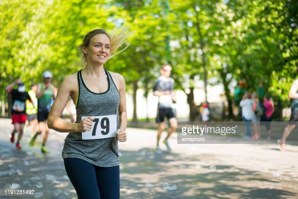 happy young woman running marathon on sunny day in spring - marathon stock pictures, royalty-free photos & images