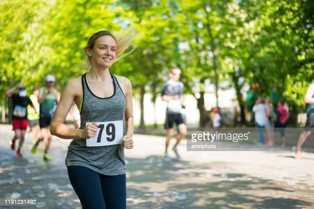 felice giovane donna correre maratona in giornata di sole in primavera - maratona foto e immagini stock