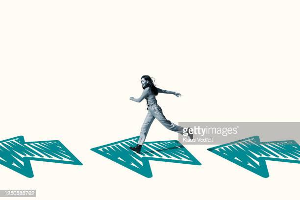 happy young woman running on turquoise arrows - part of a series stock pictures, royalty-free photos & images