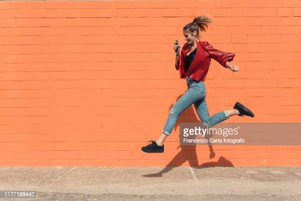 happy young woman running to school - 18 19 years stock pictures, royalty-free photos & images