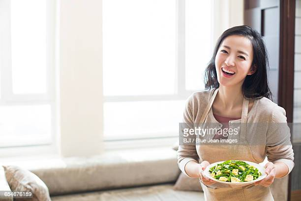 Happy young woman serving food