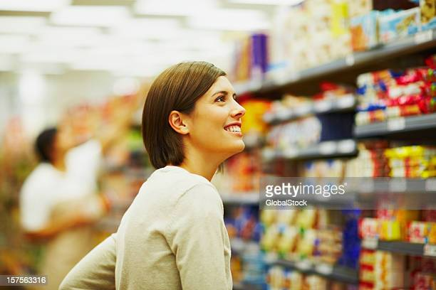 Happy young woman shopping in a supermarket