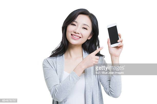 Happy young woman showing a smart phone