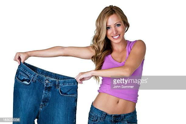 Happy young woman showing her weight loss results