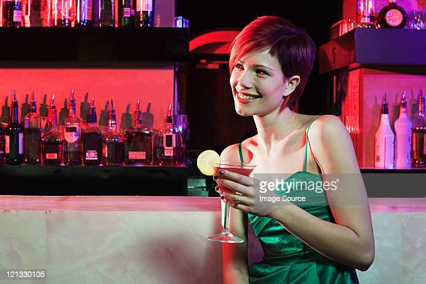 Happy young woman sitting at cocktail bar