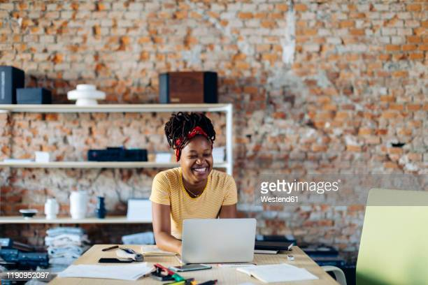 happy young woman sitting at table with laptop - funny customer service stock pictures, royalty-free photos & images