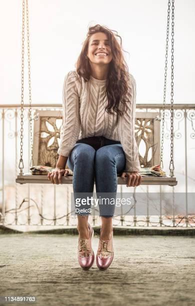 feliz mujer joven sentada en un columpio en un balcón de la casa y soñando día. - columpiarse fotografías e imágenes de stock