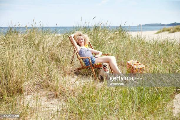 Happy young woman sitting on beach chair in the dunes