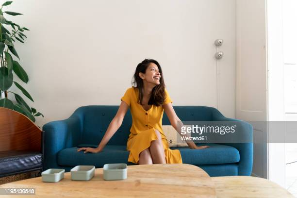 happy young woman sitting on couch looking sideways - vestido amarillo fotografías e imágenes de stock