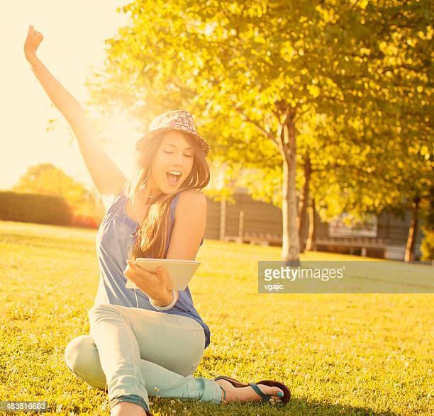 Feliz Joven mujer sentada sobre césped y escuchar música.