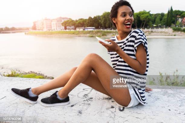 happy young woman sitting on wall at the riverside holding cell phone - black shorts stock pictures, royalty-free photos & images
