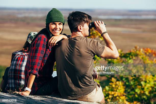Happy young woman sitting with friend using Binoculars in forest