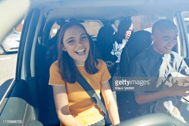 happy young woman sitting with friends in car - part of a series stockfoto's en -beelden