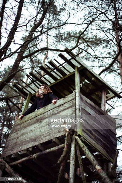 happy young woman smiles and looks out of high tree house look out - lookout tower stock pictures, royalty-free photos & images