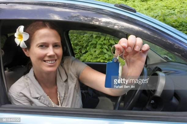 happy young woman smiling and holding her car rental key in a tropical pacific island - rafael ben ari stock-fotos und bilder