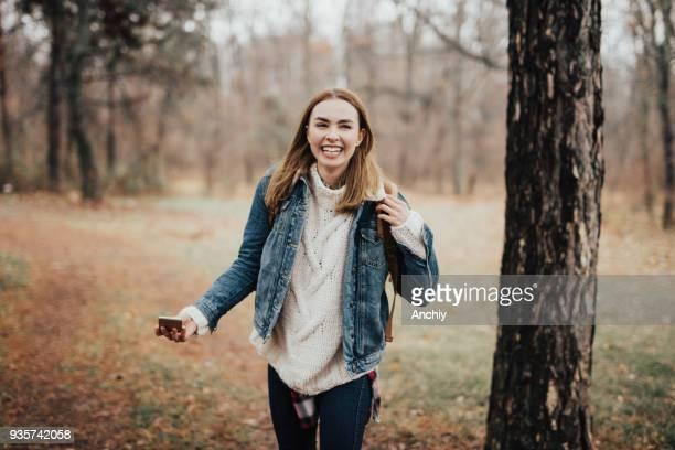 Glückliche junge Frau im Wald beim Blick in die Kamera Lächeln