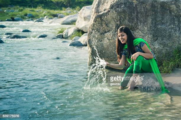 happy young woman splashing water in river - salwar kameez stock pictures, royalty-free photos & images