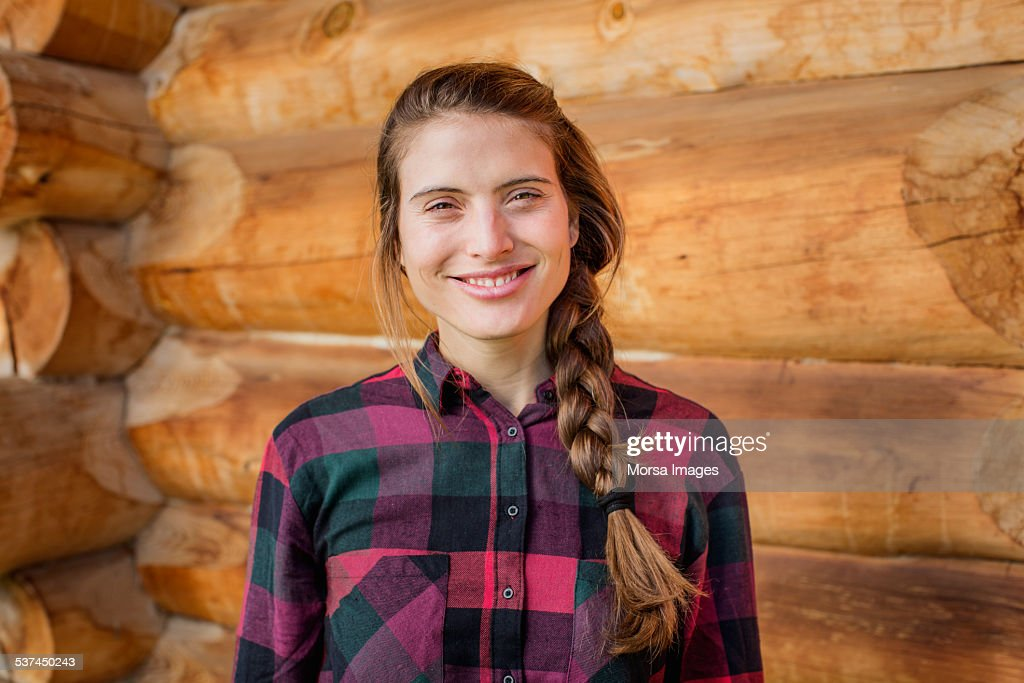 Happy young woman standing against log cabin : Stock Photo