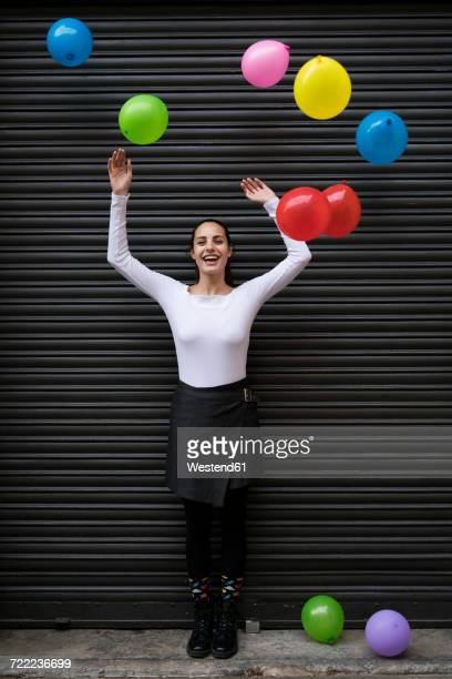 happy young woman standing in front of black roller shutter with flying balloons - flying solo after party bildbanksfoton och bilder