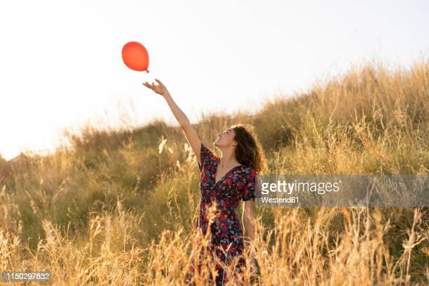 happy young woman standing in summer meadow, letting go of a red balloon - loslassen aktivitäten und sport stock-fotos und bilder