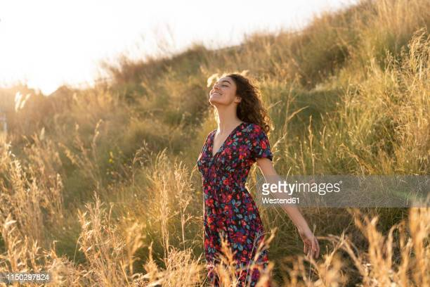 happy young woman standing in summer meadow - robe à motif floral photos et images de collection