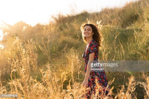 happy young woman standing in summer meadow - floral pattern dress stock pictures, royalty-free photos & images