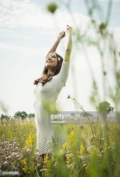 Happy young woman standing on flower meadow