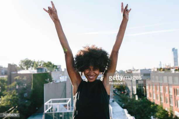 Happy young woman standing on rooftop in Brookly making victory sign