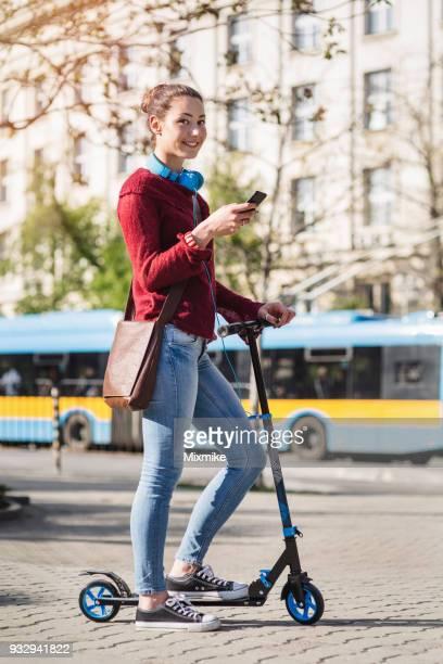 Glückliche junge Frau auf der Straße mit ihrem Roller und SMS auf dem Handy