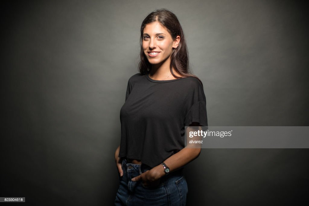 Happy Young Woman Standing With Hands In Pockets : Stock Photo