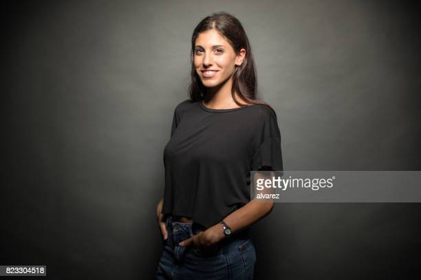 happy young woman standing with hands in pockets - three quarter front view stock pictures, royalty-free photos & images
