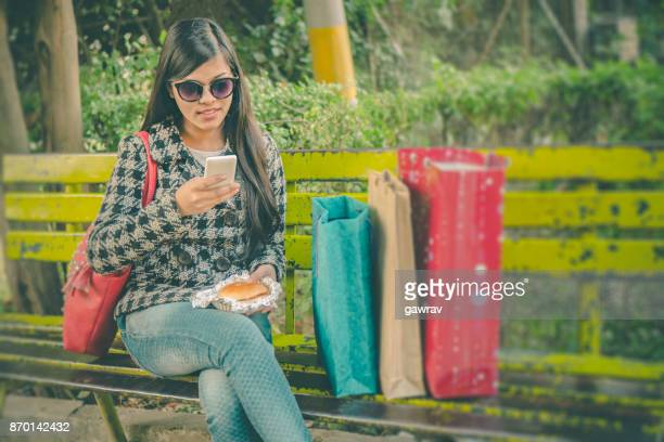Happy young woman taking break while shopping.