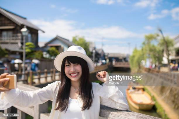 Happy young woman taking picture on old wooden bridge
